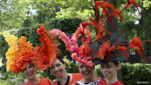 A group of racegoers poses for photographers on the first day of the Royal Ascot horse racing festival at Ascot, southern England.