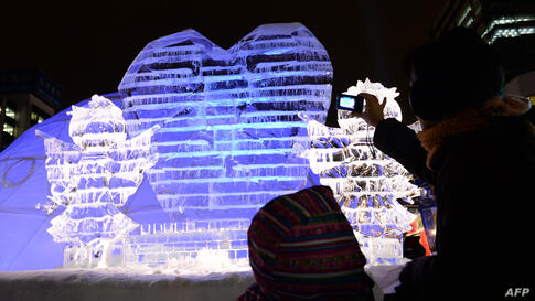 Visitors look at ice sculptures during the 65th annual Sapporo Snow Festival in Sapporo, Japan. The week-long festival started with a total of 198 snow statues on display and expects to attract around two million visitors.