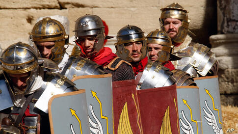 Actors dressed like Roman Legionaries in action during a demonstration in the antique theatre, in Orange, southern France, Sept. 22, 2013.