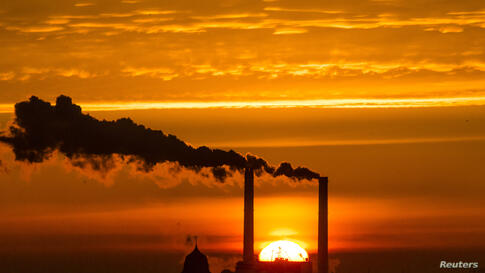 The sun rises behind the billowing chimneys of a power station in Berlin, Germany.