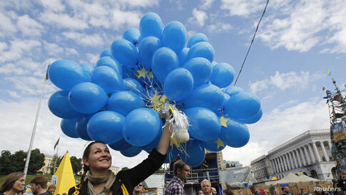 People gather in Independence Square (Maidan Nezalezhnosti) to celebrate the signing of a free-trade agreement between Ukraine and the European Union, in central Kyiv.