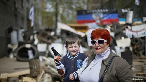 A boy with a toy gun poses for a picture in front of barricades at the police headquarters in the eastern Ukrainian town of Slaviansk.
