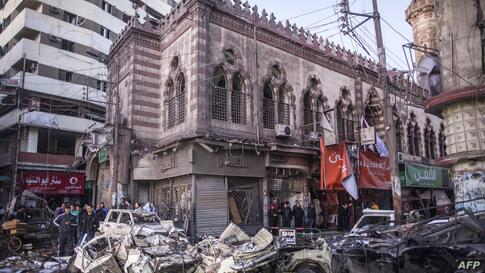 Egyptian men inspect destruction in the city of Mansura, north of Cairo, following a powerful car bomb explosion. The bombing tore through a police building in Mansura, killing at least 14 people.