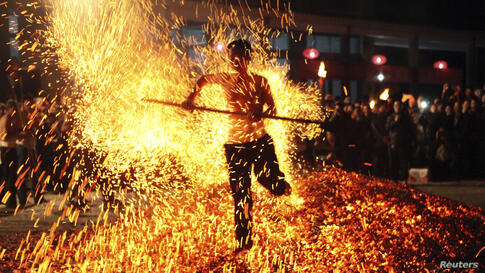 """A man walks through burning charcoal as he participates in the traditional ritual called """"Lianhuo"""", or """"fire walking"""", in Pan'an county, Zhejiang province, China, Nov. 25, 2013. Dozens of men walk over burning charcoal or firewood barefooted, as a way ..."""
