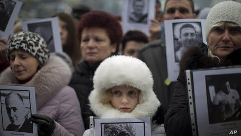 People hold photos of their relatives killed during recent clashes during a rally in Independence Square, Kyiv, Ukraine, March 2, 2014.