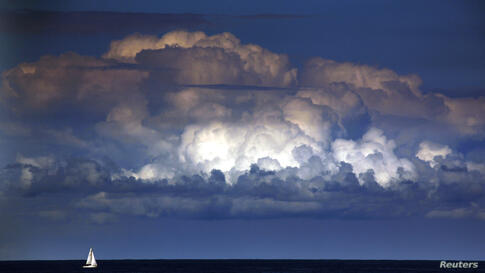 A storm cloud can be seen behind a yacht as it sails off the coast of Sydney, Australia, Mar. 31, 2014. The Bureau of Meteorology last week forecast 'warmer and drier than usual' weather extending into winter for Sydney and most of south-eastern Austra...