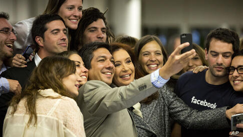 Facebook employees take a group selfie with Argentine President Cristina Fernandez, center, at the Facebook office in Buenos Aires, Argentina, May 6, 2014.