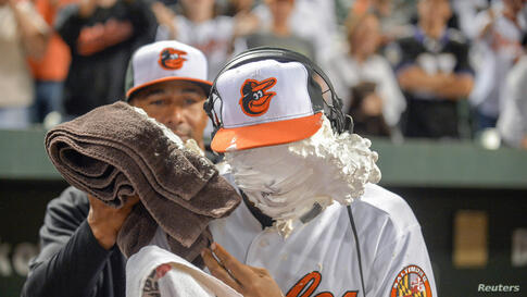 After getting his first major league base hit and his first major league home run against the Toronto Blue Jays, Baltimore Orioles second baseman Jonathan Schoop gets a shaving cream pie to the face from teammate Chris Dickers following their MLB Ameri...