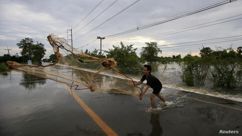 A man casts a fishing net on a flooded street at Srimahaphot district in Prachin Buri, Thailand. More than 600,000 Thais have been affected by flooding since July and more than a quarter of Thailand's provinces have been inundated.