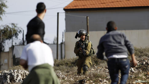An Israeli soldier shouts as he holds his weapon in front of Palestinians during clashes in Jalazoun refugee camp near the West Bank city of Ramallah. Clashes broke between stone-throwing protesters and Israeli soldiers, two days after Muhammad Mubarak...