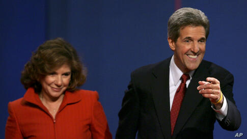 Then-Democratic presidential candidate John Kerry points toward the audience beside his wife Teresa Heinz Kerry after the presidential debate in Tempe, Arizona, October 13, 2004.
