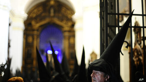 """Penitents from """"Los Dolores"""" brotherhood gather prior to a Holy Week procession in Cordoba, southern Spain. Hundreds of processions take place throughout Spain during the Easter Holy Week."""
