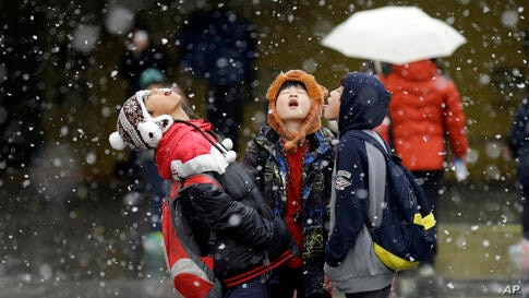 Students play in the snow in Seoul, South Korea.