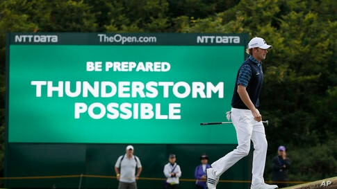 Brandt Snedeker of the U.S. walks past a digital sign showing a weather warning on the second day of the British Open Golf championship at the Royal Liverpool golf club, Hoylake, England.