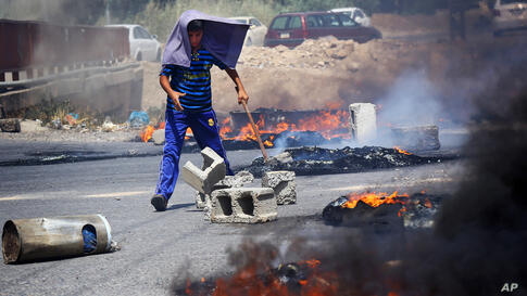 An Iraqi Kurd helps block a road during a demonstration against the fuel crisis in Irbil.