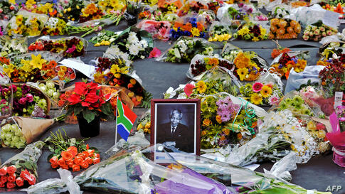 Flowers left by mourners surround a portrait of Nelson Mandela in the Sandton district of Johannesburg. Mandela, the revered icon of the anti-apartheid struggle in South Africa and one of the towering political figures of the 20th century, has died on ...