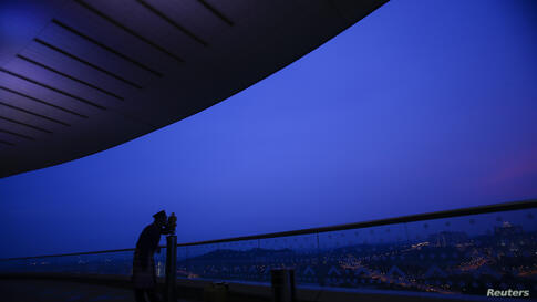 """An officer of Malaysia's Islamic authority uses a telescope to perform """"rukyah"""", the sighting of the new moon of Ramadan, in Putrajaya outside Kuala Lumpur. Muslims scan the sky at dusk in the beginning of the lunar calendar's ninth month in search of ..."""
