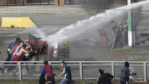 Fishermen push a part of a burnt truck against a water cannon as they clash with riot policemen during a protest against a fisheries law, which they say the government has failed to improve, in Valparaiso city, northwest of Santiago, Chile, July 2, 2014.