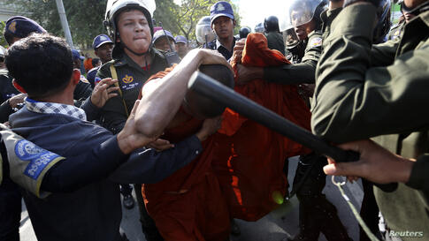 A Buddhist monk shields himself from police officers during a protest in front of the City Hall in central Phnom Penh, Cambodia. About 100 former Boeung Kak lake residents, including Buddhist monks, demanded that the government provide them with more c...