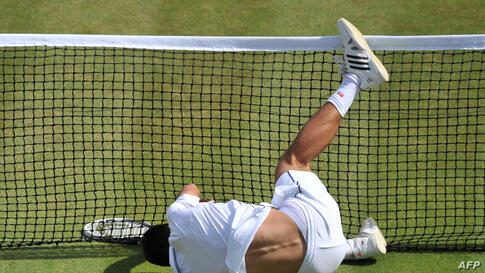 Serbia's Novak Djokovic falls into the net during the men's singles quarter-final match against Croatia's Marin Cilic on day nine of the 2014 Wimbledon Championships at the All England Tennis Club in Wimbledon, southwest London.