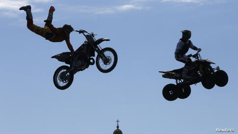 Participants perform stunts in front of St. Isaac's Cathedral during a festival of youth street culture in St.Petersburg, Russia, June 28, 2014.