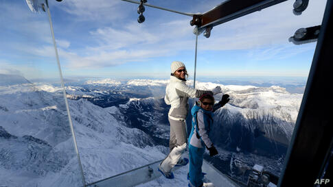 """A woman and a child stand in the """"Step into the Void"""" glass skywalk overlooking the French Alps on top of a 3842-meter peak in Chamonix. The installation, which opened to the public after three years of development, is made of three layers of glass and..."""