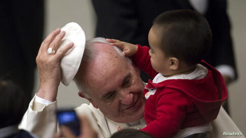 Pope Francis removes his skull cap for a child during an audience with children assisted by volunteers of Santa Marta institute in Paul VI hall at the Vatican, Dec. 14, 2013.