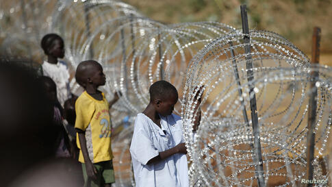 Internally displaced boys stand next to barbed wire inside a United Nations Missions in Sudan (UNMIS) compound in Juba.
