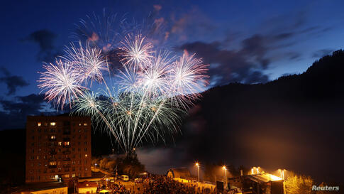 People watch fireworks explode above the Yenisei River in the town of Divnogorsk near Russia's Siberian city of Krasnoyarsk. The display was performed to mark Russia Day, the national holiday of the Russian Federation, also the Day of the Town.
