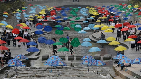 Visitors walk under the umbrellas symbolizing the earth's environment and peace along the Cheonggye stream in Seoul, South Korea.