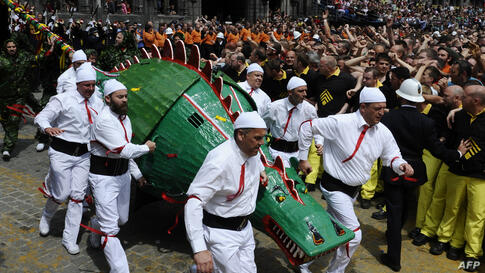 People in costumes take part in a performance showing the fight between a Saint and the dragon at Ducasse, during the Doudou folkloric festival in Mons, Belgium. The Doudou festival includes two parts, a procession at the shrine of Waltrude and a fight...