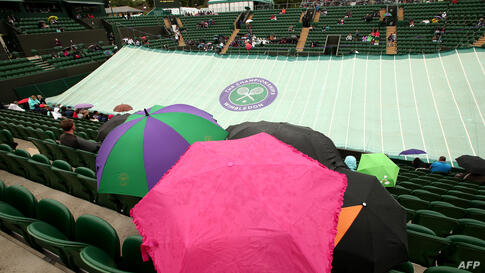 Spectators sit under umbrellas in No. 2 Court as it starts to rain on day five of the 2014 Wimbledon Championships at The All England Tennis Club in Wimbledon, southwest London.