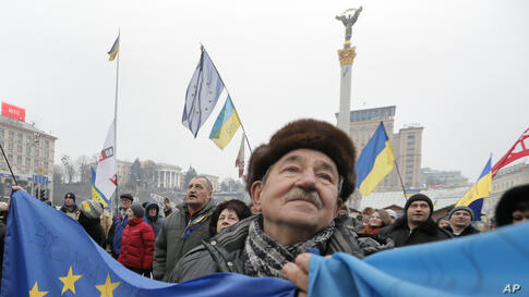 A pro-European Union activist with Ukrainian and European Union flags stands with others in Independence Square in Kyiv, Ukraine.