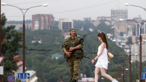 A pro-Russian separatist stands guard near a rally in support of Novorossiya (New Russia) on Lenin Square in the center of the eastern Ukrainian city of Donetsk, July 13, 2014.