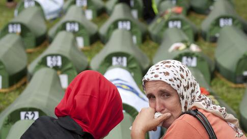 A Bosnian Muslim woman cries near coffins during a memorial ceremony and funeral in Srebrenica. Thousands of people gathered at the Potocari Memorial Center to remember the 175 victims of Europe's worst massacre since World War II.