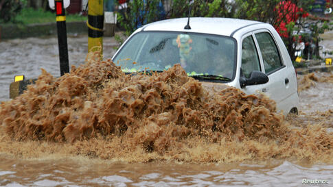 A car moves through a flooded road during heavy rains at Guwahati in the northeastern Indian state of Assam.