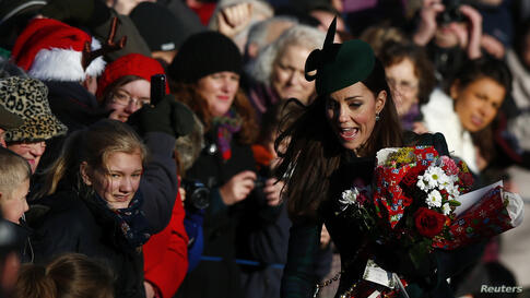 Britain's Catherine, the Duchess of Cambridge, rushes to collect flowers from well-wishers as she leaves a Christmas Day morning service at the church on the Sandringham Estate in Norfolk, eastern England.