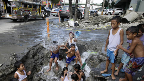 Children take advantage of a busted water pipe which was damaged overnight by a construction company as they take a bath at suburban Quezon city northeast of Manila, Philippines.