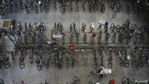 A man rides off with his bicycle outside a train station in Singapore.