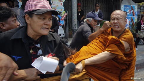 """Members of the pro-government """"red shirt"""" movement attack a Buddhist monk outside the National Anti-Corruption Commission office in Nonthaburi province, on the outskirts of Bangkok, Thailand."""