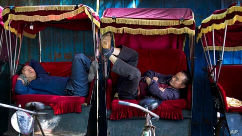 Chinese trishaw drivers take a nap while waiting for customers in an alley near the drum tower, a tourist spot in Beijing.