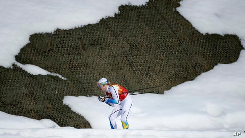 Sweden's Lars Nelson skis past a hole in the snow during the men's cross-country relay, Krasnaya Polyana, Russia, Feb. 16, 2014.