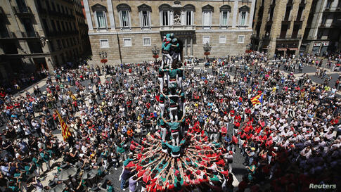 """Castellers de Sabadell form human towers during the demonstration """"Human towers for Democracy: Catalans Want to Vote"""" at Sant Jaume square in Barcelona, Spain."""