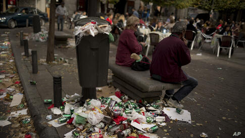 A couple sit on a public bench as garbage spills out of a full trash can during the sixth day of a garbage collectors strike, in Madrid, Spain. Street cleaners and garbage collectors, who work in the city's public parks, walked off the job in a strike ...