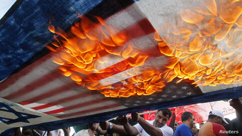 Lebanese and Palestinian protesters set fire to U.S. and Israeli flags during a demonstration to denounce Israeli air strikes on the Gaza strip, in Lebanon's southern port-city of Sidon.