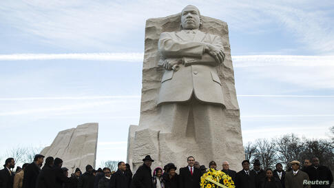 Vincent Gray (C), mayor of Washington, D.C., takes part in a wreath laying ceremony to celebrate the birthday of civil rights leader Martin Luther King, Jr. at the King Memorial in Washington.