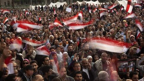 Anti-government protestors hold Egyptian flags during a demonstration at Tahrir Square in Cairo, Egypt, Wednesday, Feb. 9, 2011. Protesters appear to have settled in for a long standoff, turning Tahrir Square into a makeshift village with tens of thousand