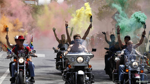 A group riding on motorcycles carry smoke torches during the 44th annual Los Angeles Pride parade in West Hollywood, California, USA, June 8, 2014.