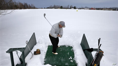 Rich Lukasik hits practice golf shots in the snow in Cream Ridge, New Jersey, USA.