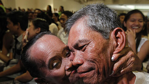 A 66-year-old bride kisses her 54-year-old groom during a mass wedding ceremony as part of a Valentine's Day celebration in Paranaque, Metro Manila February 14, 2012. (REUTERS)